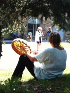 Vera Shanov plays drum outside while Pat Smith and Marcia Bendo (background) hear the beat and play their flutes in tune with nature.