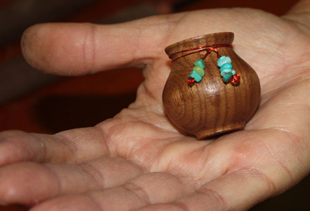 tiny wooden vessel with turquoise beads